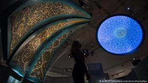 A museum staff member looks up at tilework and a bright blue dome projection in a darkened room at the 'Epic Iran' exhibition