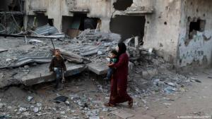 A Palestinian woman and two children survey the rubble of their home, which was destroyed by an Israeli air strike in June, Gaza Strip (photo: Mohammed Salem/Reuters)