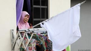 Halijah Naemat, 74, puts away a white flag after she received help from others at her home during an enhanced lockdown, amid the coronavirus disease (COVID-19) outbreak, in Petaling Jaya, Malaysia, 6 July 2021 (photo: REUTERS/Lim Huey Teng)