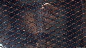 A hand of a member of the Muslim Brotherhood in a cage in an Egyptian courtroom (photo: Reuters/A. A. Dalsh)