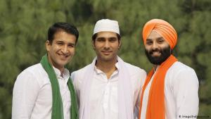 Three smiling men wearing different religious attire in the colours of the Indian flag (photo: Imago/Indiapicture)