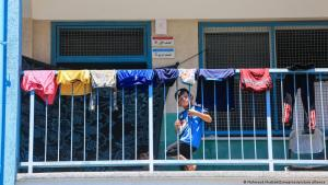 A boy on a balcony looks through railings on which clothes are drying (photo: Mahmoud Khattab/Zumapress/picture-alliance)