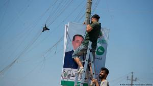 Men place an election poster for the upcoming early parliamentary elections near private generator network wires in Baghdad, Iraq, Monday, 20 September 2021 (photo: AP Photo/Hadi Mizban)
