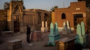 A man stands in front of a gravestone in Egypt (photo: Getty Images)