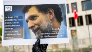 A poster depicting Osman Kavala is held up at a demonstration in Germany protesting his imprisonment in Turkey (photo: Christophe Gateau/dpa/picture alliance)