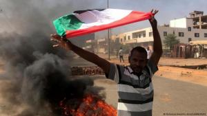 A pro-democracy activist holds up the Sudanese flag in protest at the military coup, Khartoum, Sudan (photo: Mohammed Nureldin Abdallah/Reuters)