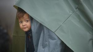 A migrant child peers from a makeshift tent at a camp housing migrants mostly from Afghanistan in Velika Kladusa, Bosnia, 12 October 2021 (photo: AP Photo)