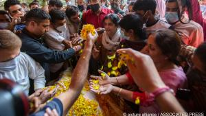 Relatives and neighbours offer flowers on the body of Makhan Lal Bindroo, a prominent chemist from Hindu community, during his funeral in Srinagar, Indian controlled Kashmir, on 6 October 2021 (photo: AP Photo/Mukhtar Khan)
