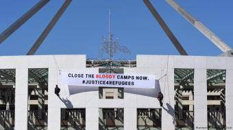 Demonstrators protesting refugee policy abseil down Australian parliament