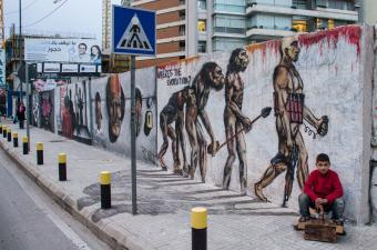 Abed, 11, a Syrian refugee in Beirut, sitting in front of graffiti by Karim Tamerji, entitled ′Evolution′. Since the beginning of the civil war in Syria, the conflict has spilt over into Lebanon, in the form of both suicide attacks and a huge immigrant influx