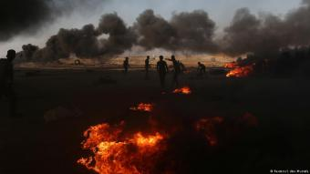 Palestinian demonstrators are seen as smoke rises from burning tyres during a protest marking the 70th anniversary of Nakba, at the Israel-Gaza border in the southern Gaza Strip, 15 May 2018 (photo: REUTERS/Ibraheem Abu Mustafa)