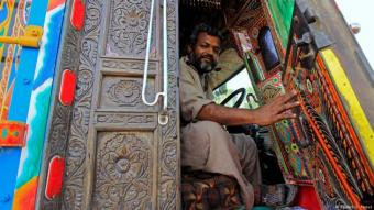 A driver opens the door to the carved wooden cab of his decorated truck