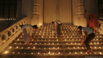Three people light candles in Colombo in memory of the victims of the Easter Day bombings (photo: picture-alliance/dpa/M. Swarup)