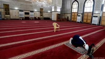 Imam prays alone in a mosque in Baghdad Iraq.