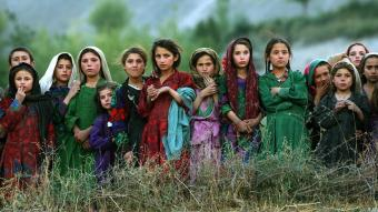 Afghan girls watch UN workers unloading a helicopter (photo: AP)