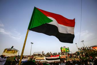 Sudanese flag waved by protesters during a demonstration to demand Sudan's transition to democracy, 12 April 2019 (photo: Getty Images/AFP/Ashraf Shazly)
