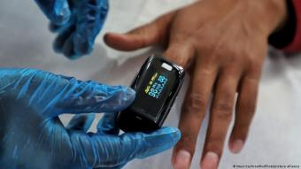 A health worker uses an oximeter to check the oxygen level of a person at a school turned COVID-19 centre in Uri, Baramulla, Jammu and Kashmir, India on 18 May 2021 (photo: Nasir Kachroo/NurPhoto)