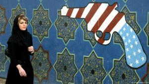 Iranian woman walks past graffiti of a gun with the design of an American flag