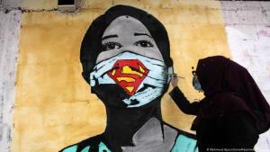 Artist puts finishing touches to a graffito warning against coronavirus (photo: Mahmoud Ajjour/Zuma Press/Imago images)